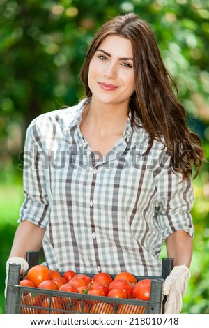 Young Woman Farmer carrying a crate of tomatoes - stock photo