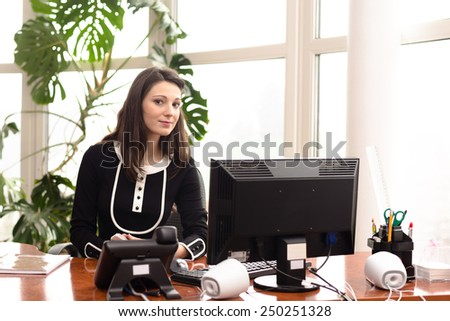 Young woman fashion designer speaking on phone at work place with computer - stock photo