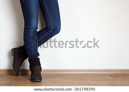 Young woman fashion legs in blue jeans and brown boots on wooden parquet floor on white background - stock photo