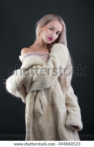 Young Woman Fashion Model dressed in white fur coat on blue background