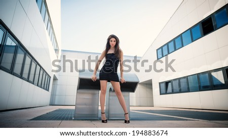 Young woman fashion portrait wearing black dress and modern building as background.