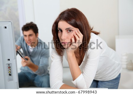 Young woman fed up with boyfriend playing video game - stock photo
