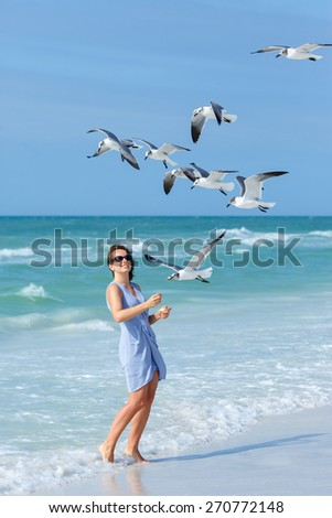 Young woman feeding seagulls on tropical beach, Florida summer holiday vacation - stock photo