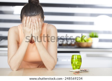 Young woman feeling bad and pills on table  - stock photo