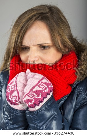 Young woman feeling cold  trying to keep warm, shaking and shivering, wearing gloves  and knitted scarf over gray background - stock photo