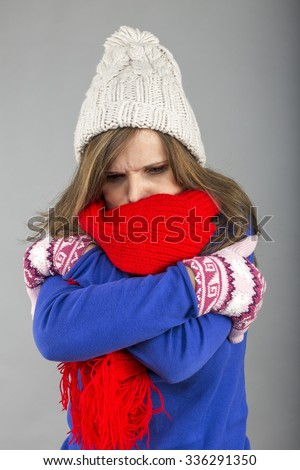 Young woman feeling cold  trying to keep warm, shaking and shivering, wearing gloves,hat  and knitted scarf over gray background - stock photo