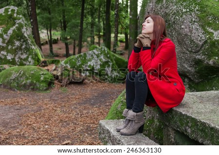 Young woman feeling depressed sitting on a stone table and bench on a forest wearing a red overcoat during winter  - stock photo
