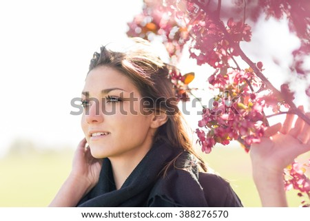 Young woman feeling happy by a blossoming apple tree in spring season - stock photo