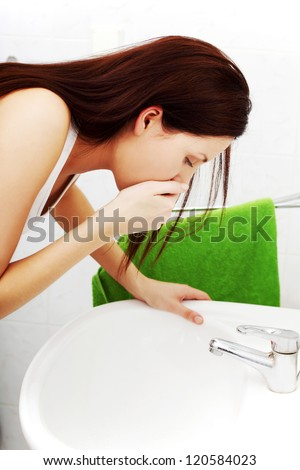 Young woman feeling sick in the bathroom.