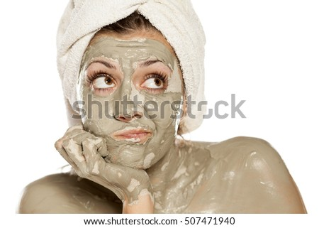 young woman feels bored with the green clay mask on her face