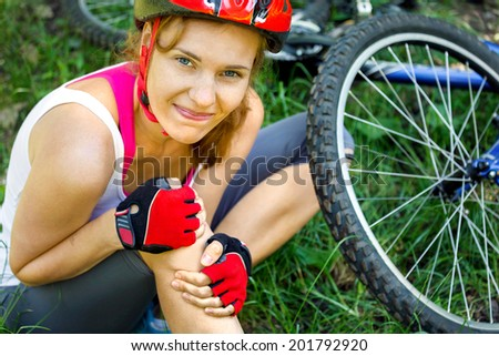 Young woman fell off mountain bike. - stock photo