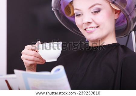 Young woman female client reading magazine and drinking hot beverage coffee tea in hairdressing beauty salon. Girl in hair rollers curlers with hairdryer dryer relaxing by hairdresser hairstylist. - stock photo