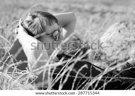Young woman female sunglasses lying back resting in high grass portrait. Black and white. - stock photo