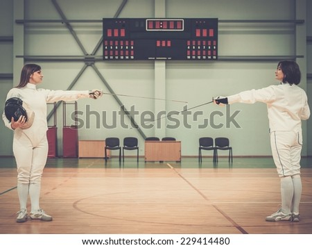 Young woman fencer and her trainer  - stock photo