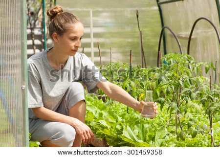 young woman fertilizes plants from a glass bulb - stock photo