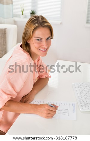Young Woman Filling Survey Form With Pen At Desk - stock photo