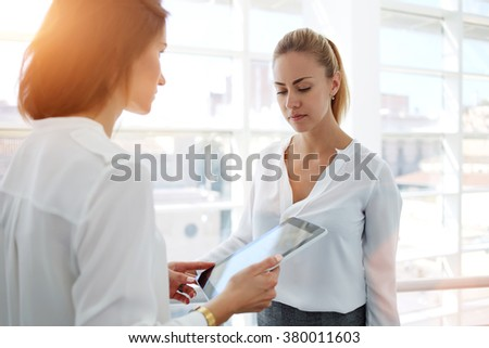 Young woman financier consulting with proud ceo about project on digital tablet while standing in modern office interior, confident female associates during work break analyzing strategy on touch pad