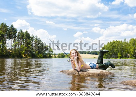 young woman fishing in pond during summer - stock photo