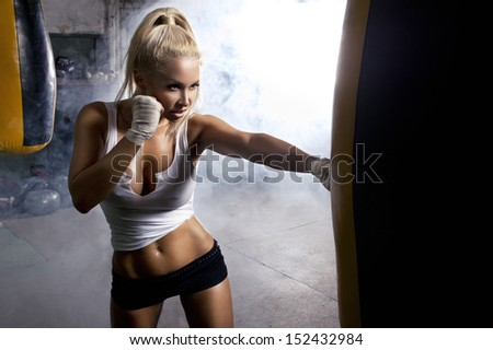 Young woman fitness boxing in front of punching bag - stock photo