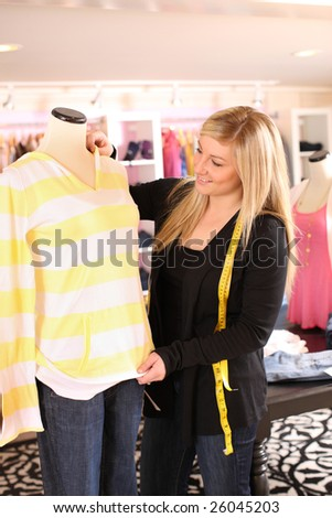 Young woman fitting manikin with clothing - stock photo