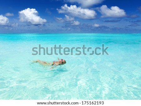 young woman floating on the surface of the warm, turquoise tropical sea. vacation in the Caribbean. girl on the beach Bahamas. young woman on the Hawaiian beach