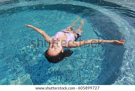 Young woman floating on the water surface of the swimming pool