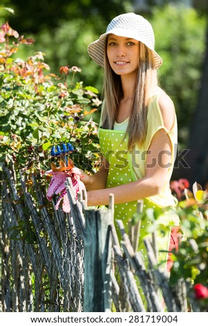 young woman florists in apron working in the garden
