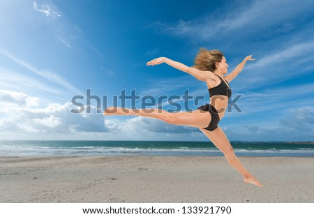 Young woman flying in a graceful jump at the beach - stock photo
