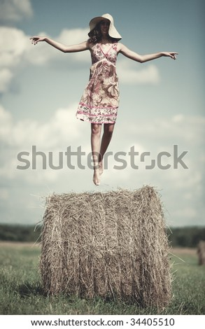 Young woman flying over haystack in a field.
