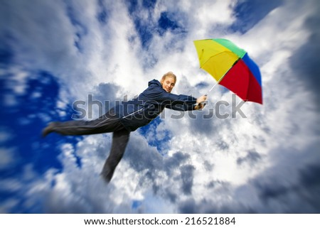 Young woman flying with umbrella in the sky - stock photo