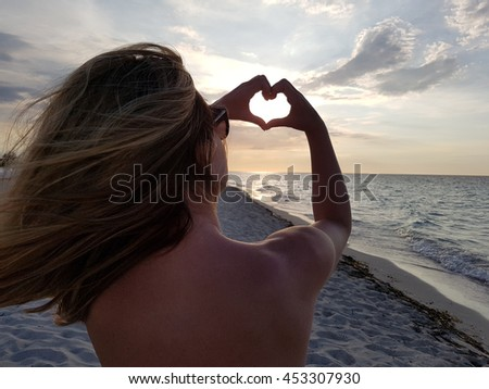 Young woman forming a heart with her hands toward the sun - stock photo