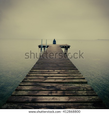young woman freedom and enjoy with morning the nature on the mountain lake, Italy. Beautiful young woman with arms stretched out standing on a wood bridge. Happy feeling good and relaxing at the lake. - stock photo