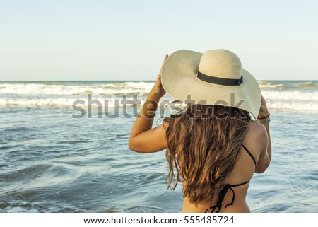 Young woman from behind, wearing beach summer hat looking to the sea. Rear view.