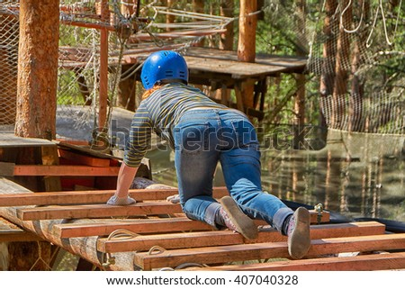 Young woman from the back in adventure rope park - stock photo