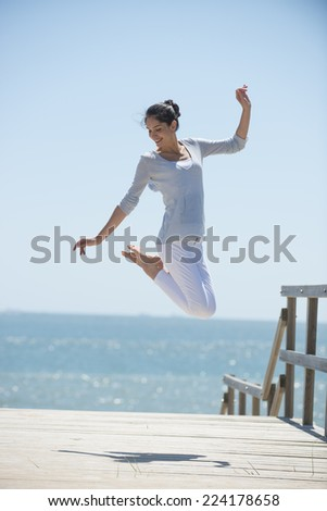 young woman full of energy jumping on a pontoon in front of the sea on a sunny day - stock photo