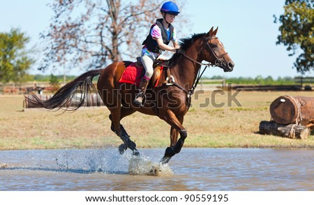 Young woman gallops a horse through water - stock photo