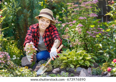 Young Woman Gardener Planting Flowers In The Garden. People, Gardening,  Planting Of Flowers