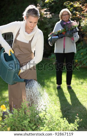 Young woman gardening with her grandmother - stock photo