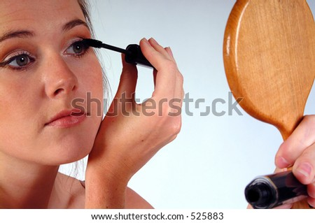 Young woman gazing into a hand mirror whilst applying her mascara. Shot against a white background. - stock photo