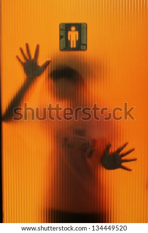 Young woman gazing sadly out a window, image turned on it's side for an eerie effect - stock photo