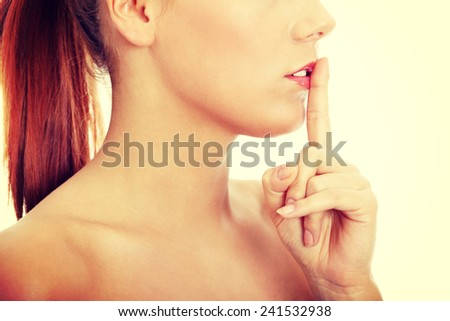 Young woman gesturing for quiet. - stock photo
