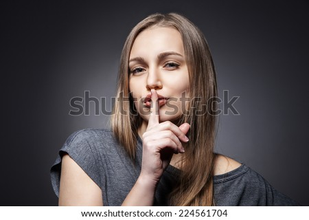 Young Woman Gesturing for Quiet or Shushing over dark grey background - stock photo