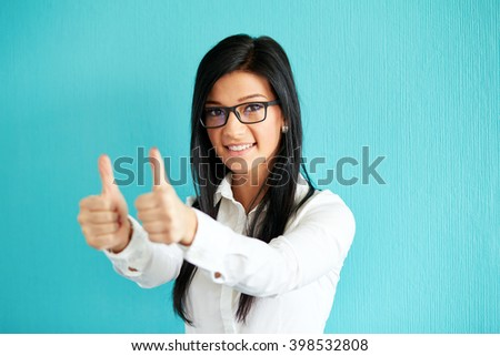 Young woman gesturing ok with thumbs up, on a blue background - stock photo