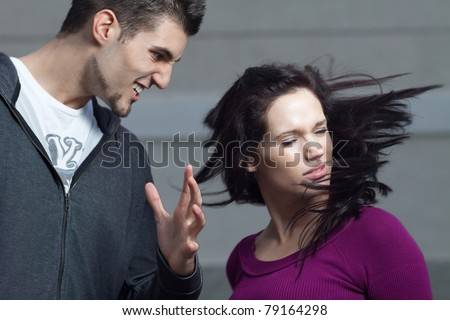 Young woman gets slapped by her boyfriend. Action shot with selective focus on her face. Shallow depth of field. - stock photo
