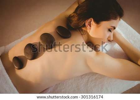 Young woman getting a hot stone massage in therapy room - stock photo