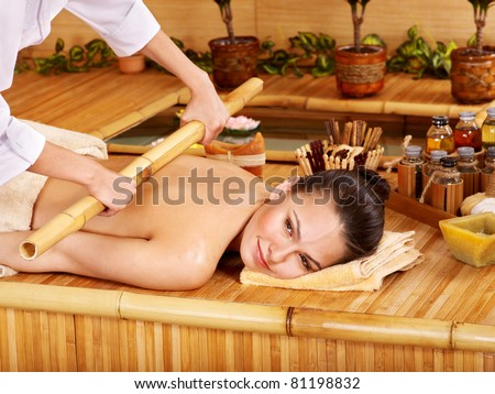 Young woman getting bamboo massage. - stock photo