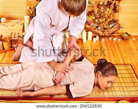 Young woman getting bamboo massage. Male therapist. - stock photo