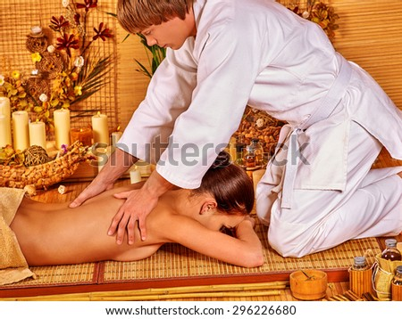 Young woman getting bamboo massage. Male therapist kneels.