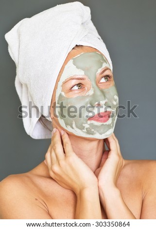 young woman getting facial mask - stock photo