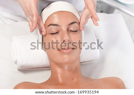 Young woman getting facial massage in beauty saloon, laying relaxed. - stock photo